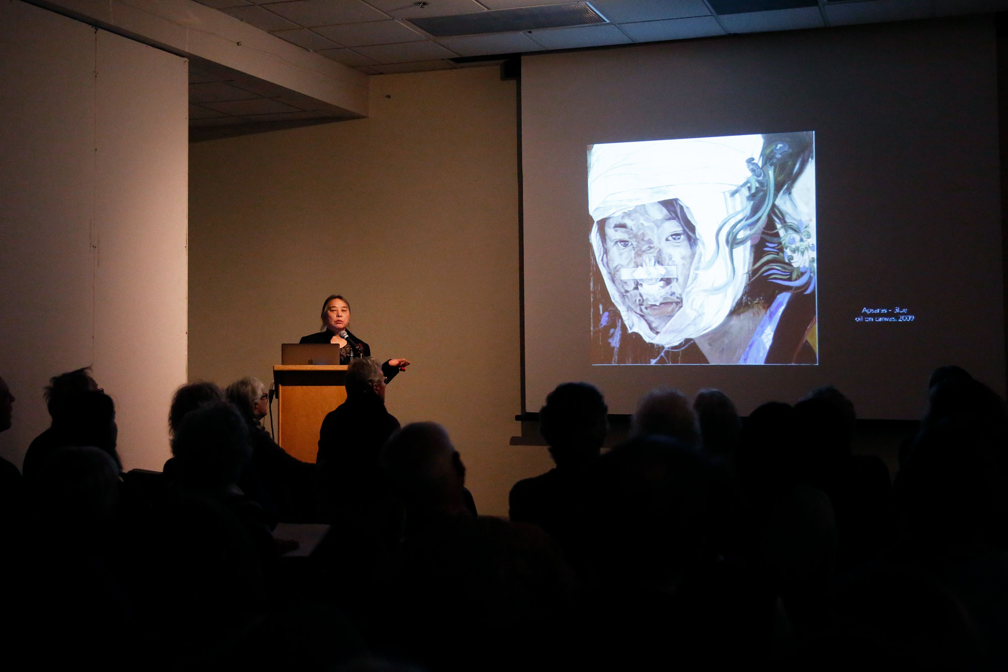 Artist Hung Liu shares her life story through her artwork in a powerpoint presentation delivered at the MAH. In one of her more recent oil paintings from 2009, she created portraits dedicated to those who suffered through the 2008 earthquake in China. Photo by Casey Amaral
