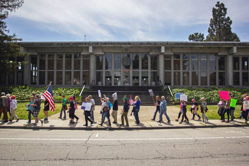 Demonstrators march down Water Street in front of the Santa Cruz County Government Center. Organizers requested that marchers remain on the sidewalk throughout the protest to ensure everyone's safety. Meanwhile, passing cars and buses honked their horns in approval. Photo by Alonso Hernandez