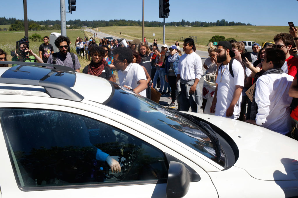 A driver argues with demonstrators  who refused to let any vehicles  beyond the picket line. Photo by Cal Tobias