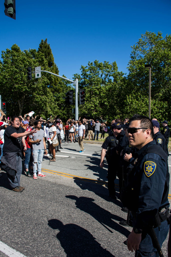 A line of police officers face the group  of protesters shortly before they broke  through the picket line. Photo by Alonso Hernandez