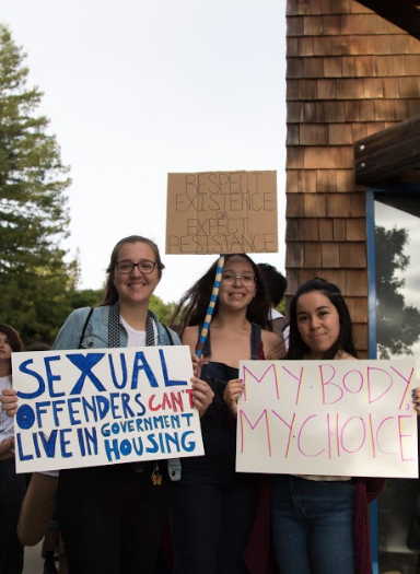 "Three Students who took part part of the march around campus reached the end of march at the Oakes Learning Center. Their signs read, ""Sexual Offenders Can't Live In Government Housing,"" ""Respect Existence or Expect Resistance"" and ""My Body My Choice."" Photo by Danielle De Rosario."