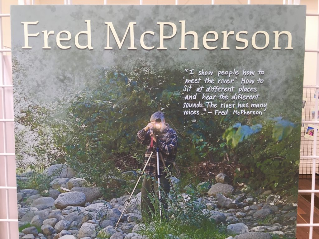 """A photo of Fred McPherson behind his camera and tri-pod. His face is obscured, and the camera is flashing. A quote from McPherson says in white letters """"I show people how to 'meet the river'. How to sit at different places and hear the different sounds. The river has many voices."""""""
