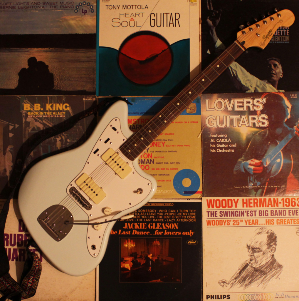 A guitar on an assemblage of records.