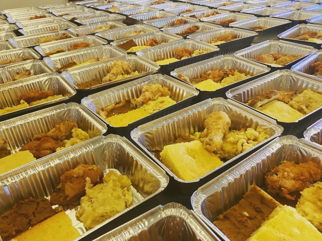 Rows of boxed lunch containing cornbread and fried chicken.