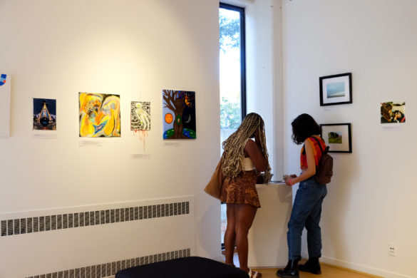 Pieces of art hang along white walls, displaying the submissions of student artists. In the corner, there are two guests in the gallery looking at the artwork.